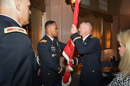 Colonel David Turner (center) passes the Sacramento District's colors to Col.  Michael J. Farrell during a change of command ceremony for the U.S. Army Corps of Engineers Sacramento District at the Masonic Temple in Sacramento, Calif., July 10, 2013.