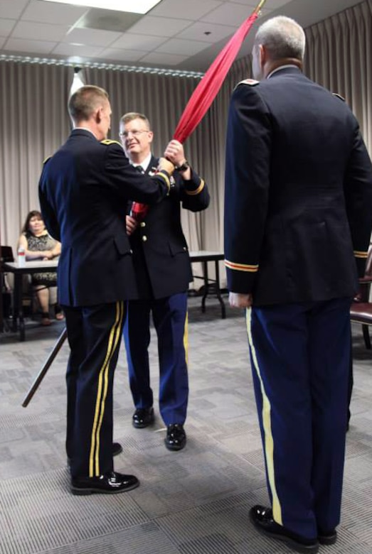 Colonel Richard Pannell, middle, accepts the flag from Southwestern Division commander Brig. Gen. Thomas W. Kula as Pannell assumes command of the Galveston District in ceremonies July 9.