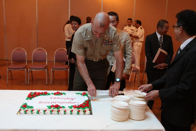 Lt. Col. Mike Carriero, Marine Corps Air Station Iwakuni S-1 and manpower director, cuts the cake after a retirement ceremony for local national employees at the Landing Zone