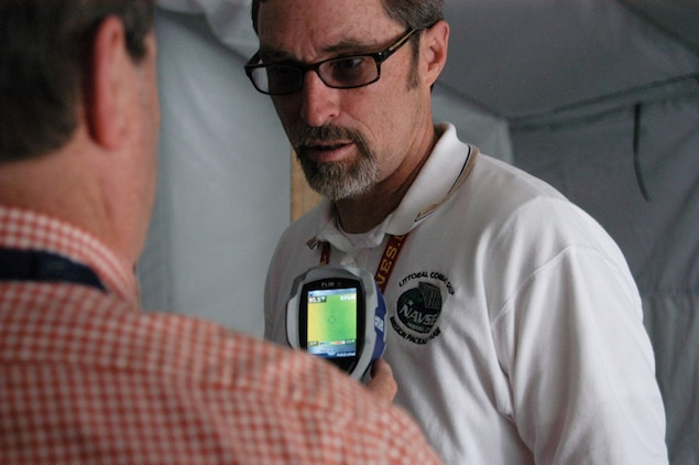 Naval Surface Warfare Center Panama City Division (NSWC PCD) engineers Bob Backus (left) and Ray Sheffield (right) use a hand held thermal imaging device April 26, 2013 to determine heat levels inside a tent being used for energy absorbtion and monitoring research conducted at NSWC PCD.