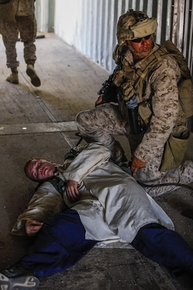 """A Marine rifleman, right, from 3rd Battalion, 1st Marine Regiment of Marine Corps Base Camp Pendleton, Calif., searches a Marine roleplayer from the Tactical Training Exercise Control Group, left, after he was """"killed"""" during a long-range raid training exercise in the desert southeast of Marine Corps Air Station Yuma, Ariz., June 3. The job of the roleplayer is to provide realistic simulation and opposition for Marines during training exercises."""