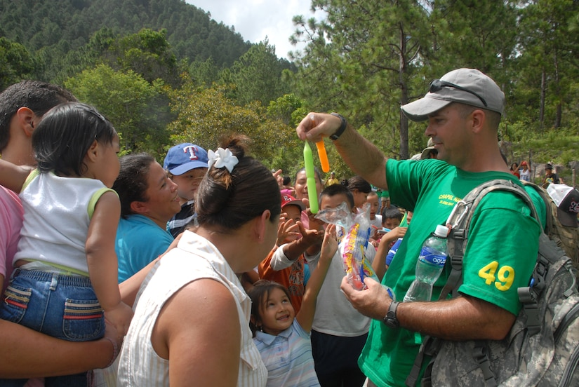 Master Sgt. Steven Fadden, J4 maintenance noncommissioned officer in charge, hands out ice-pops to children during the June 29, 2013, Chapel Hike. More than 100 volunteers from JTF-Bravo gathered together for the bi-monthly Chapel Hike to deliver 120 bags of groceries and supplies to 86 families.