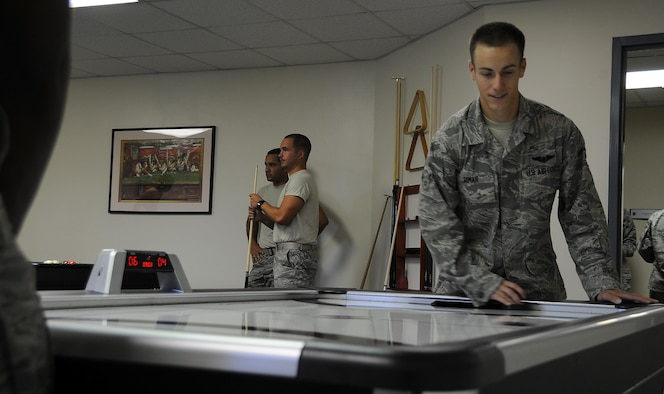 ALTUS AIR FORCE BASE, Okla. – Airman 1st Class Paul Rimar, 97th Training Squadron student, plays air hockey in the Airman Resilience Center, July 11. The Airman Resilience Center is a provided for all Airmen and their dependents to encourage better mental, social, physical and spiritual fitness. It has five classrooms available for training use, an electronic gaming area, theater and a game room. (U.S. Air Force photo by Airman 1st Class Franklin R. Ramos / Released)