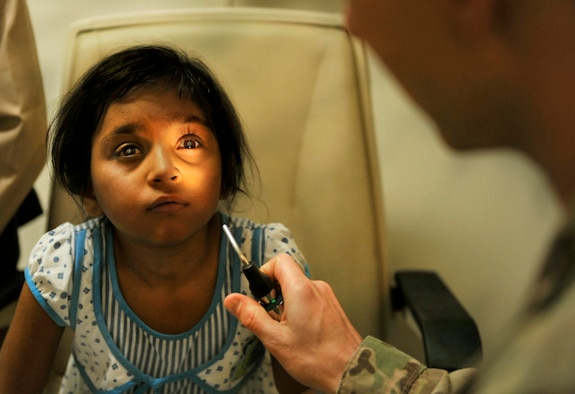 Maj. Marcus Neuffer, 455th Expeditionary Medical Group ophthalmologist, examines and compares the eyes of a six-year-old Afghan patient in the Joint Craig Theater Hospital Ophthalmologist Clinic on Bagram Airfield, Afghanistan, July 6, 2013. He recently completed a surgery on her right eye to correct a cataract. The girl had been diagnosed with cataracts in both eyes in May. A cataract is an eye disease in which the clear lens of the eye becomes cloudy and opaque, causing a decrease in vision. The lens is replaced in surgery, without treatment a cataract can result in a complete loss of vision. (U.S. Air Force photo/ Staff Sgt. Stephenie Wade)