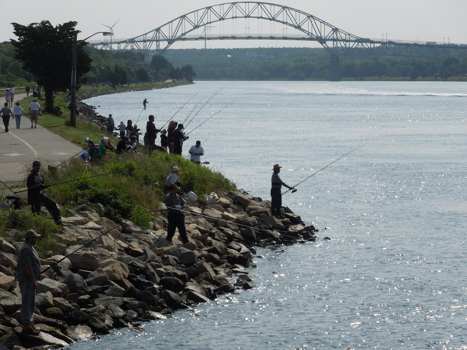 With the Bourne Bridge in the background of a 2013 file photo, anglers flock to the rocky shores of the Cape Cod Canal recreation area in Buzzard's Bay to try their hand at landing some fish on an overcast weekend.
