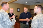 Col. Barrett Holmes (left) meets with Michael Byrne, Glen Sachtleben, and Capt. Chris Colbert, as the four prepared to board a UH-60 helicopter Aug. 28 to conduct an initial damage assessment of North Carolina. Holmes is the defense coordinating officer for U.S. Army North's Region IV Defense Coordinating Element. Byrne is a federal coordinating officer, and Sachtleben, an operations officer, both with the Federal Emergency Management Agency. Colbert is the pilot of the helicopter from the 3rd Infantry Division's Combat Aviation Brigade that conducted the flight mission in support of FEMA, which is the overall lead for the federal response effort for Hurricane Irene.