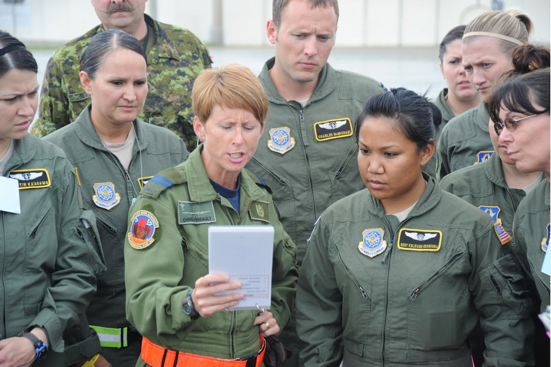 Capt. Chris Perrault, a flight nurse with the Royal Canadian Air Force 426th Squadron Medical Flight, reads from the pre-flight checklist before a training mission with American 36th Aeromedical Evacuation Squadron and 43rd AES at Pope Field, N.C., on July 12, 2013.  The American and Canadian flight crews and medical crews joined forces to enhance inter-service interoperability and provide continuation training, said RCAF Warrant Officer James Oddie, the 426th flight warrant officer.  (Air Force Photo by Tech. Sgt. Peter R. Miller)