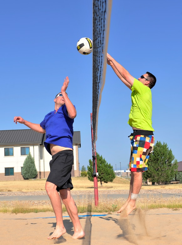 Joseph Hennigan, 460th Operations Support Squadron, right, blocks a hit from Mathew Holley, 460th OSS, during the annual four-on-four sand volleyball tournament July 11, 2013, at Buckley Air Force Base, Colo. Hennigan scored half of the team's points and continuously cheered on his teammates. (U.S. Air Force photo by Airman 1st Class Darryl Bolden Jr./Released)