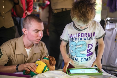 Corporal Caleb E. Haynes, an assistant team leader for Company E., Battalion Landing Team 2nd Battalion, 4th Marines, 31st Marine Expeditionary Unit, and a native of Laurel, Md., watches 6-year-old Brody, recently diagnosed with diabetes, play a game on his tablet during a visit here, July 10. Twelve Marines and Sailors of the 31st Marine Expeditionary Unit joined 22 crew members of the USS Bonhomme Richard (LHD-6) during a visit to the Mater's Rehabilitation Center and Mater's Children Center to brighten the spirits of the patients. The 31st MEU is the Marine Corps' force in readiness for the Asia Pacific region and the only continuously forward-deployed MEU.