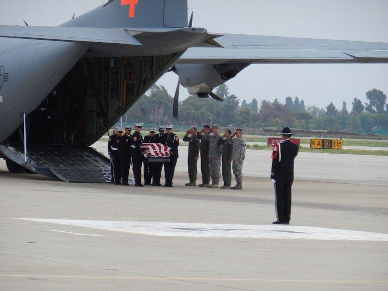 Colonel Paul Hargrove and air crew members from the 146th Airlift Wing salute as brethren firefighters serving as honor guard carry the bodies of Christopher Mackenzie age 30 and Kevin Woyjeck age 21 from the back of a C130-J aircraft stati...oned at Channel Islands Air National Guard Station. After getting approval from the Secretary of Defense, the 146th served as transport for these California natives to return home. The two men were killed last week working as a firefighting hotshot crew battling the Yarnell fire in Prescott, Arizona. (U.S. Air Force photo by Maj. Kimberly Holman)