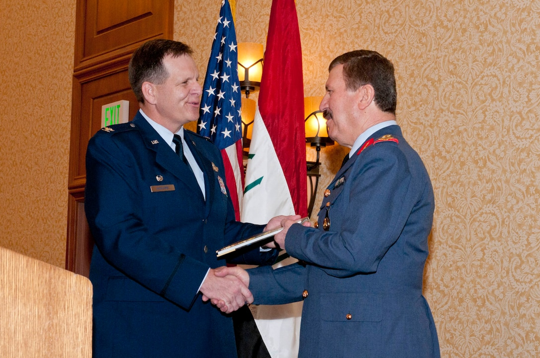 Col. Mick McGuire (left), presents a gift to Staff Lt. Gen. Hamad Ameen Ahmed Mam Seeny Anwer during the inaugural graduation ceremony of two Iraqi F-16 pilots.  (U.S. Air National Guard photo by Tech Sgt. Hollie Hansen/Released)