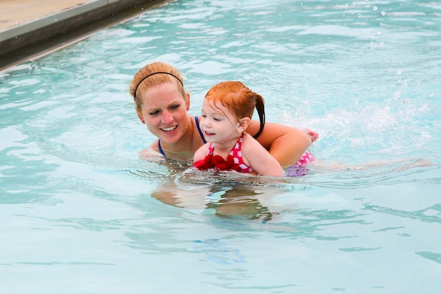 Anna Simpson, Marine Corps Community Services water safety instructor, swims with Emma Feeney, daughter of Sgt. Kenneth Feeney from Marine All-Weather Fighter Attack Squadron 224, during the Exceptional Family Member Program swimming session at the Laurel Bay community center pool, July 2.