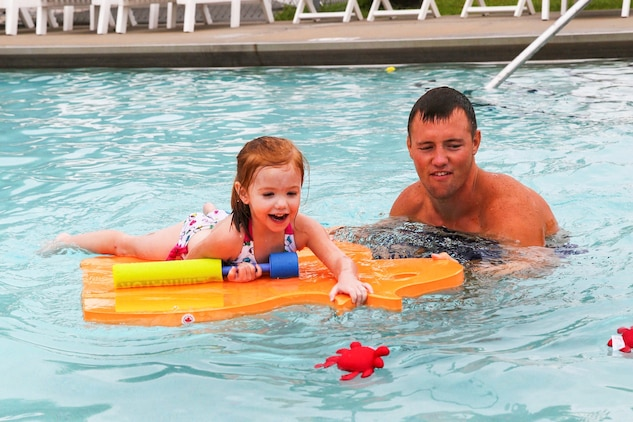 Haileigh Feeney, daughter of Sgt. Kenneth Feeney from Marine All-Weather Fighter Attack Squadron 224, swims with Luke Johnson, Marine Corps Community Services water safety instructor, during the Exceptional Family Member Program swimming session at the Laurel Bay community center pool, July 2.
