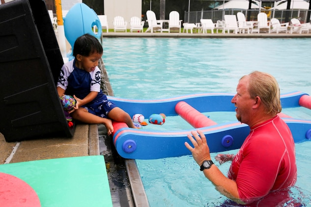 David Cunningham, a child with autism plays with Josh Cole, Marine Corps Community Services aquatics director, during the Exceptional Family Member Program swimming session at the Laurel Bay community center pool, July 2.
