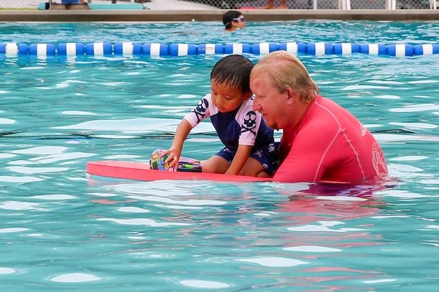 David Cunningham, son of Asheley and Ricardo Cunningham, plays with Josh Cole, Marine Corps Community Services aquatics director, during the Exceptional Family Member Program swimming session at the Laurel Bay community center pool, July 2. David is diagnosed with autism and has participated in numerous swimming sessions provided by the EFMP.