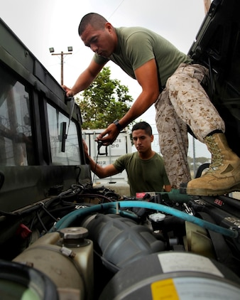 MARINE CORPS BASE CAMP PENDLETON, Calif. (July 11, 2013) Sergeant Thomas G. Ochoa (right), motor transportation maintenance chief, Command Element, 15th Marine Expeditionary Unit, instructs Pfc. Diego Retamozo(left), administrative clerk, CE, 15th MEU, on how to properly check fluids on a MII 52 High Mobility Multipurpose Wheeled Vehicle during weekly vehicle maintenance at the 15th MEU's motor pool aboard Camp Pendleton, Calif., July 11. Marines with the MEU conduct preventative maintenance weekly on tactical vehicles to ensure unit readiness. Ochoa, 29, is from Los Angeles. Retamozo, 20, is from Perth Amboy, N.J. (U.S. Marine Corps photo by Cpl. Emmanuel Ramos/Released)
