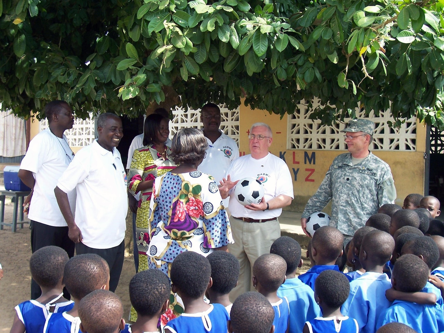 Doug Friez, a project advisor with the State Partnership Program, presents a soccer ball to a teacher at a school in Ghana, Africa. Friez and Lt. Col. Mark Tibor (right) were in the country to provide a Disaster Management Workshop. At left are employees with Ghana's National Disaster Management Organization, or NADMO, who participated in the workshop.