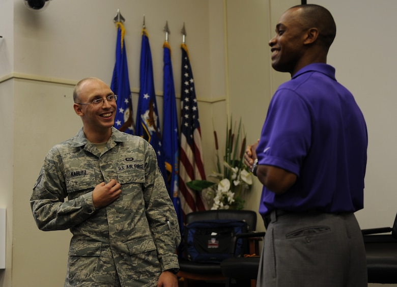 "Senior Airman Kier Kablitz, a weather and communications evaluator with 2nd Combat Weather Systems Squadron, left, interacts with Leonard Wheeler, a former National Football League player and ""game on"" presenter, right, during a ""game on"" presentation at the Vincent Airman Leadership School auditorium at Hurlburt Field, Fla., July 11, 2013. Wheeler challenged more than 50 Air Commandos in attendance with games targeted at enhancing their communication skills. (U.S. Air Force Photo / Senior Airman Joe McFadden)"