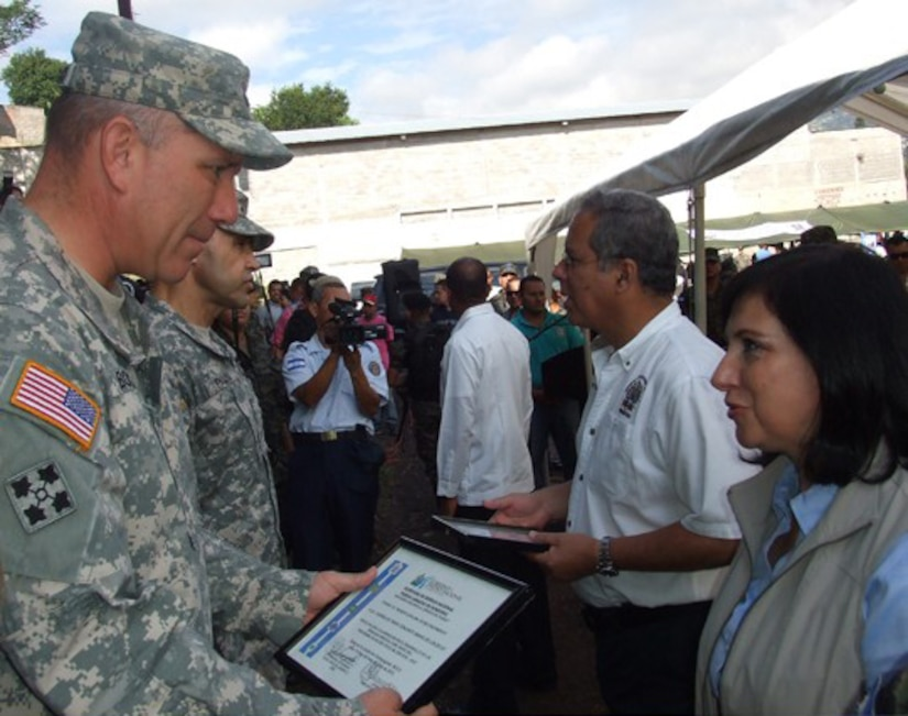 Joint Task Force –Bravo Commander, Col. Thomas Boccardi accepts an appreciation award  from the Honduran First Presidential Designate Maria Antonieta Guillen de Borgran (Honduran equivalent to the U.S. vice president) and the Honduran Armed Forces (HOAF), during an award ceremony in Tegucigalpa for providing Medical Readiness Training Exercises, which aided its one-million Honduran citizen, July 13. JTF-Bravo conducts MEDRETEs throughout Central America each year in support of U.S. Southern Command's humanitarian assistance and disaster relief programs. In coordination with the Offices of Security Cooperation and partner nation Department of Health Officials in all seven Central American countries, JTF- Bravo has treated more than 341,500 medical patients, 67,400 dental patients and 14, 300 surgical patients over the past 20 years.