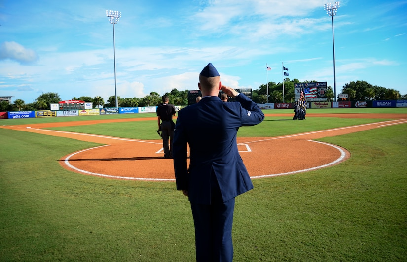 Airman 1st Class Michael Reeves, 628th Air Base Wing Public Affairs broadcaster, salutes as the Joint Base Charleston Honor Guard marches off the field during Military Appreciation Night July 13, 2013, at the Joseph P. Riley Jr. ballpark in Charleston, S.C. Reeves sang the National Anthem to a crowd of more than 5,000 fans. (U.S. Air Force photo/ Staff Sgt. Anthony Hyatt)