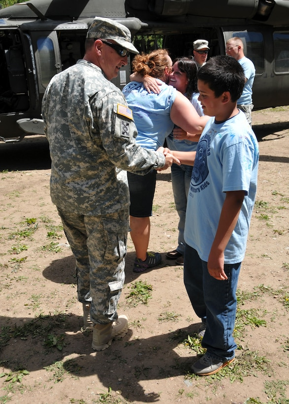 Montana National Guard Adjutant General, Maj. Gen. Matthew Quinn, shakes hands with a young camper attending Camp Runnamucka, held at Camp Rotary located near Monarch, Mont. on June 27, 2013. (Air Force photo/Senior Master Sgt. Eric Peterson)