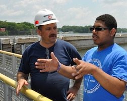 Chris Sherek, an Old Hickory Hydropower trainee at the Old Hickory Lock and Dam from the U.S. Army Corps of Engineers Nashville District talks with John Fitzgerald, Jr., a student from Memphis, Tenn about operation procedures at the Old Hickory Lock and Dam on June 27, 2013. Fitzgerald was part of a group of 17 students who attended the Tennessee State University Engineering Department's four-week National Summer Transportation Institute program that introduces students to various aspects of engineering.