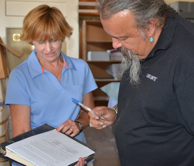 GALLUP, N.M., -- Ronald Maldonado, supervisory archaeologist for the Navajo Nation Historic Preservation Department and Julie Price, cultural resources project manager, U.S. Army Corps of Engineers, Omaha District, complete the paperwork transferring 425 sacred relics to the Navajo Nation July 9, 2013.
