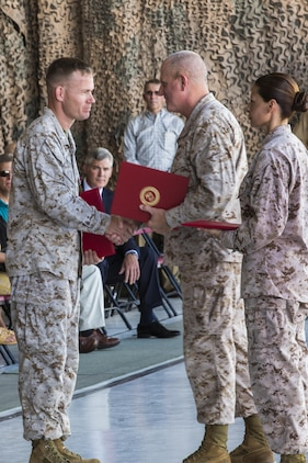 "Following the Deactivation Ceremony of Marine Attack Squadron 513, Lt. Col. Samuel Smith, the VMA-513 commanding officer, left, receives his certificate of retirement from Maj. Gen. Steven Busby, the commanding general of 3rd Marine Air Wing, center, and Sgt. Maj. Raquel Painter, the sergeant major of VMA-513, right, July 12, at the squadron hanger on Marine Corps Air Station Yuma, Ariz. Smith is the final commanding officer of ""The Flying Nightmares."""