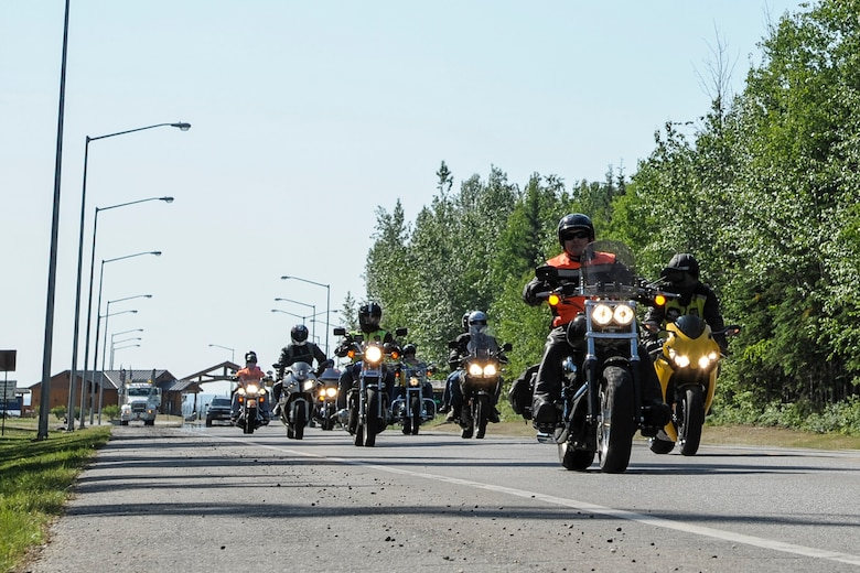U.S. Air Force service members roll away from Hursey Gate during a motorcycle mentorship group ride June 22, 2013, Eielson Air Force Base, Alaska.  Mentorship rides are an opportunity for members of the Eielson community to not only practice motorcycle safety, but also to build camaraderie and meet other riders.  (U.S. Air Force photo by Airman 1st Class Peter Reft/Released)
