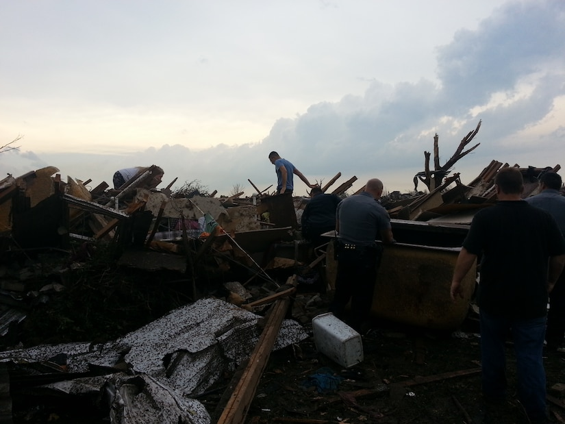 MOORE, Okla. -- Volunteers search for pets amidst debris after an EF-4 tornado struck the area May 20, 2013.  (Courtesy photo)