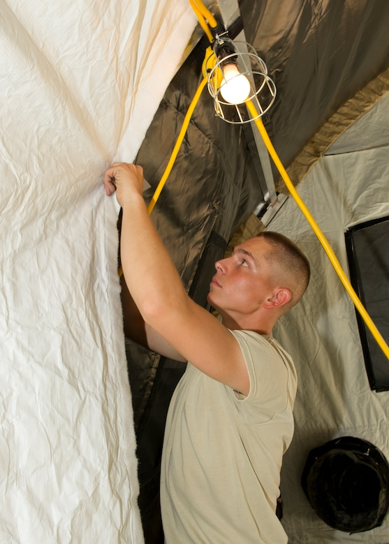 Airman 1st Class Bryce Bigboy, 49th Materiel Maintenance Squadron structural apprentice, attaches a liner to a small shelter tent during a Basic Expeditionary Airfield Resources Base five-day training exercise at Holloman Air Force Base, N.M., July 10. The liner adds an additional layer to protect occupants from hot or cold weather conditions. (U.S. Air Force photo by Senior Airman Kasey Close/Released)