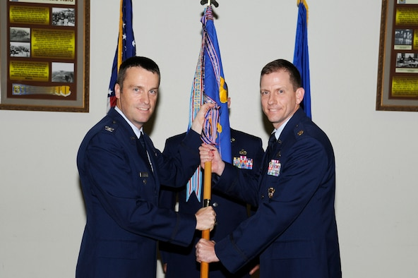 GOODFELLOW AIR FORCE BASE, Texas -- Col. Thomas Schmidt, 17th Training Wing Vice Commander, passes the 17th Comptroller Squadron guidon to the incoming commander, Maj. Brian Vance, during the Change of Command ceremony, July 11. The change of command ceremony is steeped in tradition and allows units to witness the formal command transfer from one officer to another.  (U.S. Air Force photo by Staff Sgt. Austin Knox)