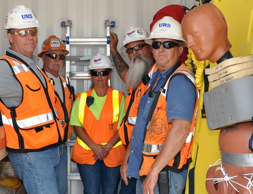 At Olmsted Locks and Dam construction project, some of the original first responders in the equipment conex with the emergency medical technician are (from left to right) casting yard manager Bob Wheeler, carpenter general foreman Bobby Miller, site EMT Melissa Crisman, ironworker superintendent Glen Bragg and batch plant superintendent Rich Hamilton. The crash dummy is used for rescue drills that train removing an injured worker on a stretcher.