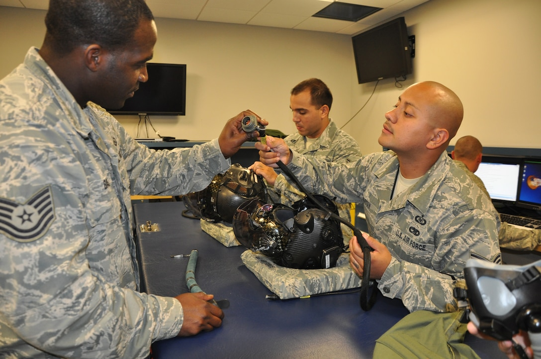 Tech. Sgt. Andre Baskin (left) and Tech. Sgt. Lemuel Velazquez (right), inspect the optical cable of the F-35 Lightning II helmet June 24, 2013 at the 33rd Fighter Wing, Eglin AFB, Fla. The members are part of the 33rd Operations Support Squadron Aircrew Flight Equipment Flight and ensure the pilots have well-maintained gear, which provides enhanced situational awareness, targeting information and symbology capabilities displayed on the visor of the helmet. (U.S. Air Force photo by Maj. Karen Roganov)