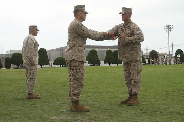 Col. Robert V. Boucher, Marine Corps Air Station commanding officer, passes the Sword of Office to Sgt. Maj. Keith Massi during a relief and appoint ceremony July 12, 2013. Boucher assumed the billet of station commanding officer in the ceremony that took place before the relief and appointment.
