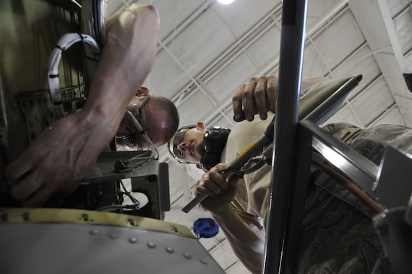Airman 1st Class Lawerence Bowman, left, Detachment 303 Aircraft Maintenance Squadron structural maintenance apprentice, and Staff Sgt. Aaron Williams, 442nd AMXS structural maintenance apprentice, cleans foreign object debris off the A-10 Thunderbolt II's wing at Whiteman Air Force Base, Mo. July 1, 2013. This is a requirement for each operational procedure done on the A-10 jet to prevent damage from FOD left behind. (U.S. Air Force photo by Airman 1st Class Keenan Berry/Released)
