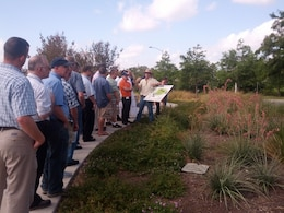 A group of students participate look at a biorentention area, or rain garden, during low impact development training.