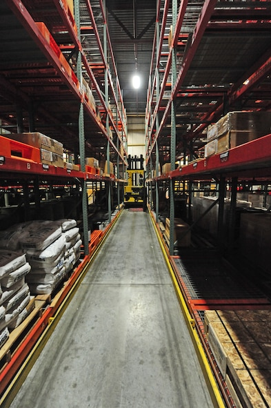 Airman 1st Class Terrell Grant, 509th Logistics Readiness Squadron central storage journeyman, drives a hyster up an aisle to pull a piece of equipment off of a shelf for a customer at the central storage warehouse at Whiteman Air Force Base, Mo., June 25, 2013. Central storage journeymen like Grant issue out thousands of parts each day. (U.S. Air Force photo by Staff Sgt. Nick Wilson/Released)