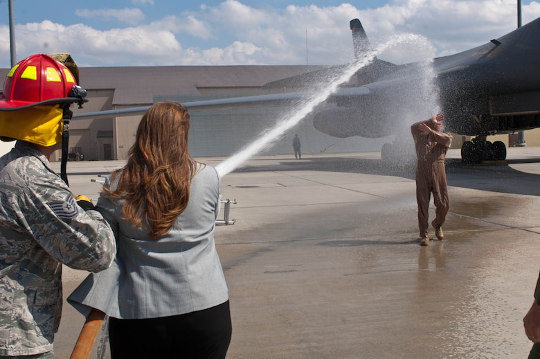 Tania Schepper, wife of Lt. Col. Timothy Schepper, 28th Operations Group senior evaluator, hoses down her husband after his return flight from Southwest Asia at Ellsworth Air Force Base, S.D., July 15, 2013. Schepper is the first B-1 bomber aviator in history to achieve 5,000 flying hours. The pilot with the next highest amount of hours at Ellsworth has flown 3,270 hours. (U.S. Air Force photo by Airman 1st Class Zachary Hada/Released)