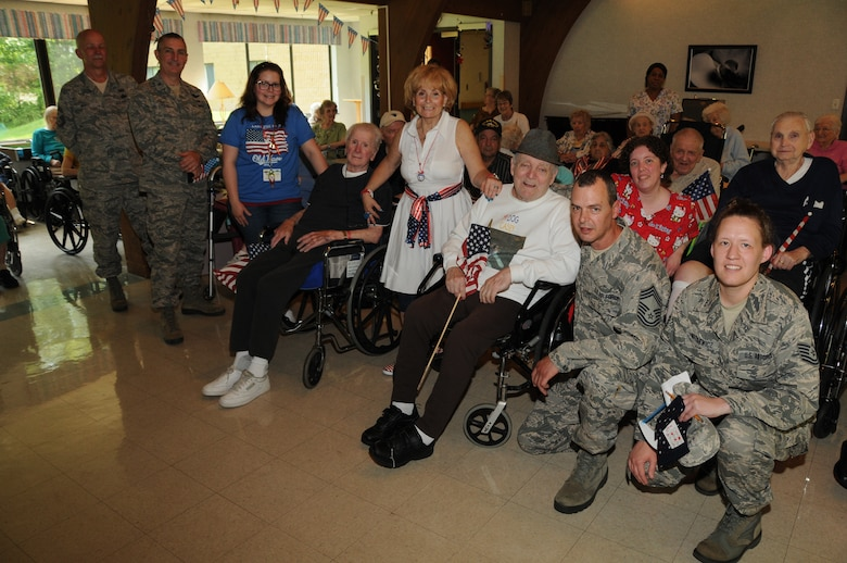 Events Director, Randie Duretz (center in white), of The Luther Woods Nursing Home and Rehabilitation Center in Horsham, Pa. extended an invitation to wing members to join clients there to celebrate their Military Appreciation month on May 21. Among the visitors to the home were Command Chief Master Sgt. Richard Mertz (left), 111th Fighter Wing Commander, Col. Howard Eissler, plans and resources superintendent for the 111th Communications Flight, Chief Master Sgt. Harley Delp and the base public affairs manager, Tech. Sgt. Elisabeth Matulewicz. The assembly of over 30 veterans, spouses and parents of veterans, shared their military experiences from days gone by and thanked the current military members for their service to the country.