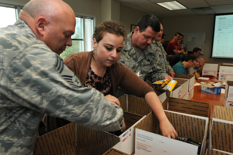 Wing volunteers spend their May 17 afternoon assisting employees from Verilgue, Inc. in building care packages destine for overseas-deployed military members. The 111th Fighter Wing Anti-Terrorism Officer, Chief Master Sgt. Paul G. Frisco, Jr. (left), Verilogue's Global Field Coordinator,  Floriana Webb and Security Forces Superintendent, Chief Master Sgt. James Finn along with others stuffed 36 boxes with sweets, letters and trinkets to thank deployed servicemen and remind them of the strong support locally for their sacrifices.