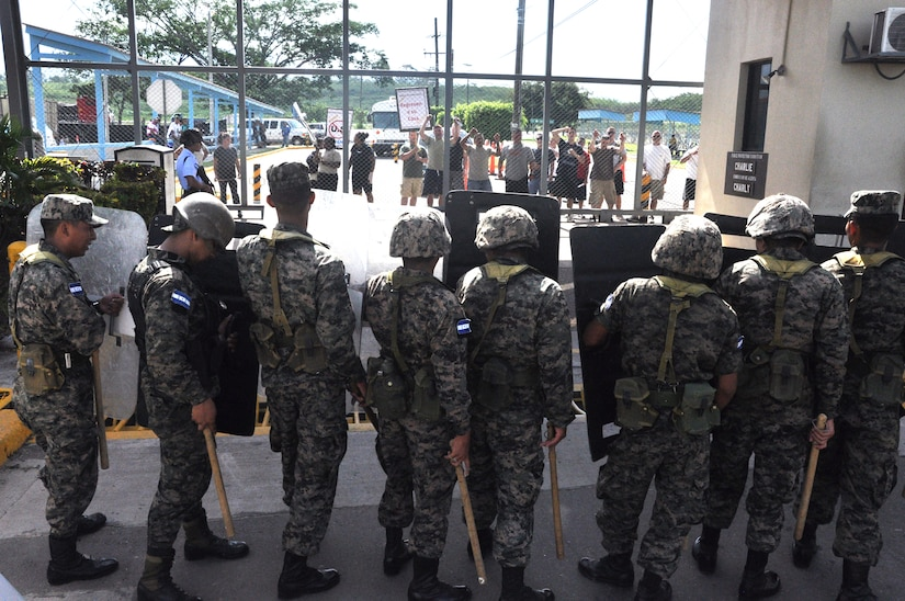 """During a Joint Task Force-Bravo Anti-terrorism/Force protection exercise, here, U.S. service members posed as Honduran protesters holding up signs saying, """"Go home,"""" as Honduran security forces were prepared for escalating protest July 17, 2013. JTF-Bravo conducts Anti-terrorism/Force Protection exercise to ensure personnel readiness, which ensures service members are ready for real world events at a moment's notice. (Photo released by U.S. Air Force Staff Sgt. Jarrod Chavana)"""