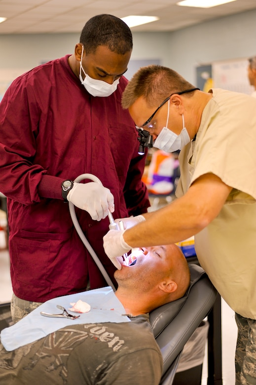"""Lt. Col. Shawn Thompson, a dentist with the 180th Fighter Wing, Ohio Air National Guard, and Senior Airman Bruce Moman, a medical technician also with the 180th FW, extract a tooth July 15, 2013, at Martin Middle School in Martin, Tenn. Thompson and about 130 service members from the Air National Guard, Naval Reserves and the Army came together in the West Tenn. Community to provide free medical care as part of Innovative Readiness Training in support of the two-week """"Hope of Martin"""" health fair. As of July 15, the medical team had extracted over 1,100 teeth. Air National Guard photo by Master Sgt. Beth Holliker (Released).   Air National Guard photo by Master Sgt. Beth Holliker (Released)."""