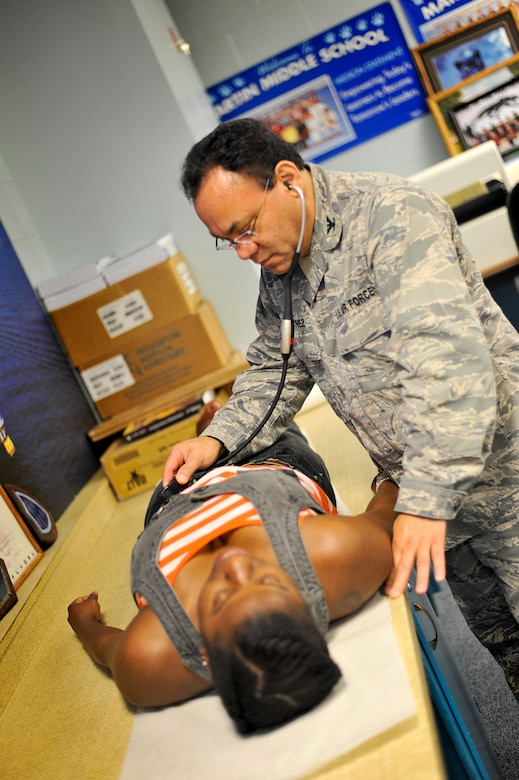 """Col. Bo Marquinez, Medical Group Commander at the 180th Fighter Wing, Ohio Air National Guard, conducts a physical exam July 15, 2013, at Martin Middle School in Martin, Tenn. Marquinez and about 130 service members from the Air National Guard, Naval Reserves and the Army came together in the West Tenn. Community to provide free medical care as part of Innovative Readiness Training in support of the two-week """"Hope of Martin"""" health fair. As of July 15, the medical team had provided medical care for over 2,000 members of the Martin and surrounding communities. Air National Guard photo by Master Sgt. Beth Holliker (Released)."""