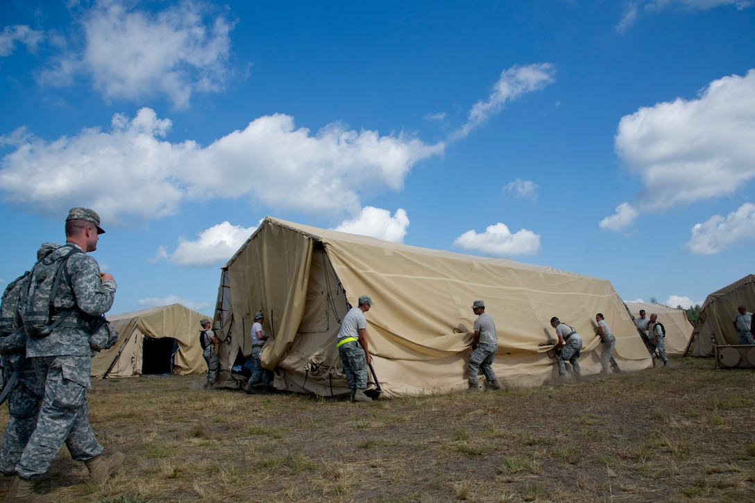 Airmen assemble and move an Utilis Compact TM60 Tall tent in preparation for Exercise Global Medic July 16, 2013. Global Medic is an annual joint-Reserve field-training exercise designed to replicate all facets of combat theater aeromedical evacuation support. (U.S. Air Force photo/Staff Sgt. Heather Cozad)