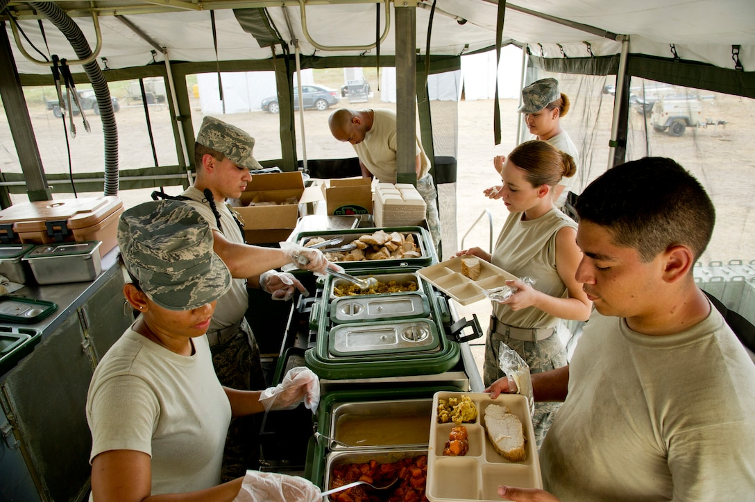 Airmen assigned to the 940th Force Support Squadron at Beale Air Force Base, Calif., serve dinner in the field in a mobile kitchen trailer during Exercise Global Medic July 16, 2013, at Fort McCoy, Wis. Global Medic is an annual joint-Reserve field-training exercise designed to replicate all facets of combat theater aeromedical evacuation support. (U.S. Air Force photo/Staff Sgt. Heather Cozad)