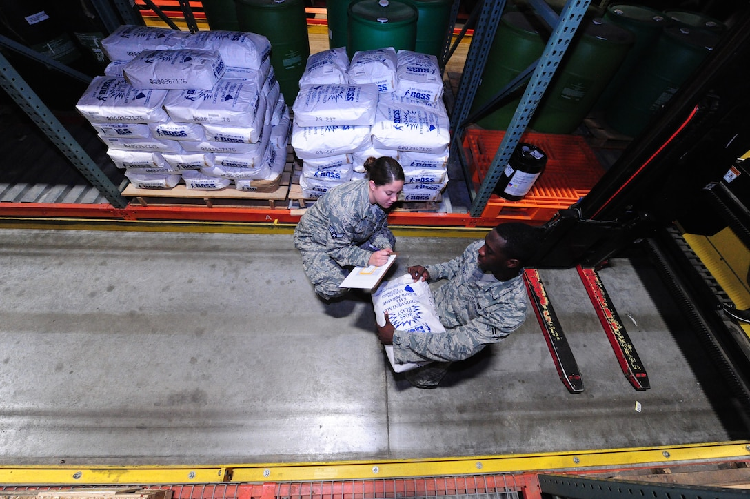 """Senior Airman Stephanie Shipwash and Airman 1st Class Terrell Grant and, both 509th Logistics Readiness Squadron central storage journeymen, document batch slot numbers and expiration dates with Airman 1st Class Terrell Grant, at the central storage warehouse at Whiteman Air Force Base, Mo., June 25, 2013. This helps Airmen prioritize items according to shelf-life and expiration dates. All items are handed to customers in """"first in, first out"""" order. (U.S. Air Force photo by Staff Sgt. Nick Wilson/Released)"""