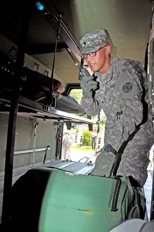 During a Honduran and American Anti-terrorism/Force protection exercise, here, U.S. Army Specialist Drew Danner, Joint Task Force-Bravo Medical Element emergency medical technician, notifies Medel he's transporting patients and would need medical assistance, when a bomb was detonated during a protest at the front gate, July 17, 2013.  JTF-Bravo conducts Anti-terrorism/Force Protection exercise to ensure personnel readiness, which ensures service members are ready for real world events at a moment's notice. (Photo released by U.S. Air Force Staff Sgt. Jarrod Chavana)
