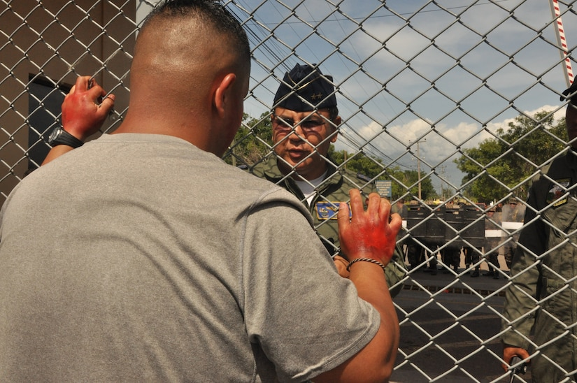"""During a Honduran and American Anti-terrorism/Force protection exercise, here, Honduran air force Lt. Col. Cristobal Vargas, Honduran air force base commander, tries to speak with the """"lead protester,"""" U.S. Army Sgt. Leobardo Villareal, the """"protesters"""" rallied outside the Soto Cano Air Base gates July 17, 2013. JTF-Bravo conducts Anti-terrorism/Force Protection exercise to ensure personnel readiness, which ensures service members are ready for real world events at a moment's notice. (Photo released by U.S. Air Force Staff Sgt. Jarrod Chavana)"""