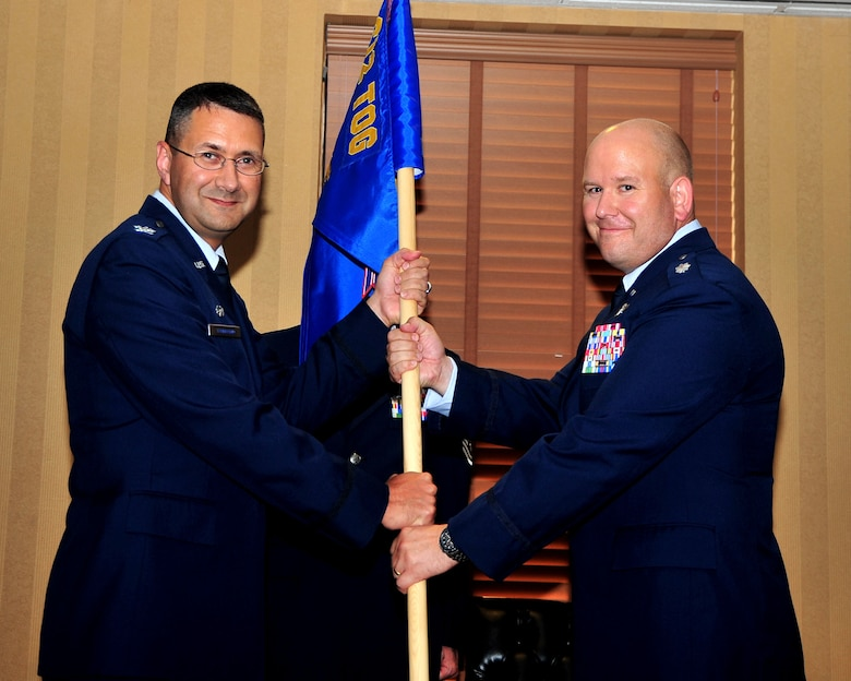 Col. Jonathan VanNoord, 612th Theater Operations Group commander, passes the 612th Support Squadron guidon to Lt. Col. Jeremy Thiel, incoming 612th Support Squadron commander, during a change-of-command ceremony on Davis-Monthan AFB, Ariz., July 16. (USAF photo by 355th Fighter Wing Public Affairs/Released)